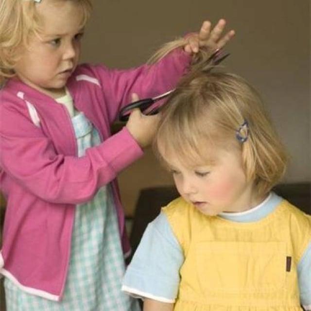 Niña cortando el cabello a su hermana