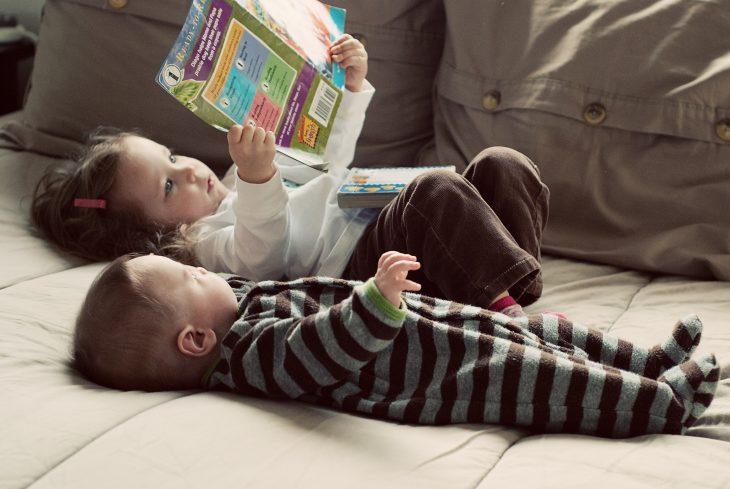 Hermana pequeña leyendo a su hermanita bebé
