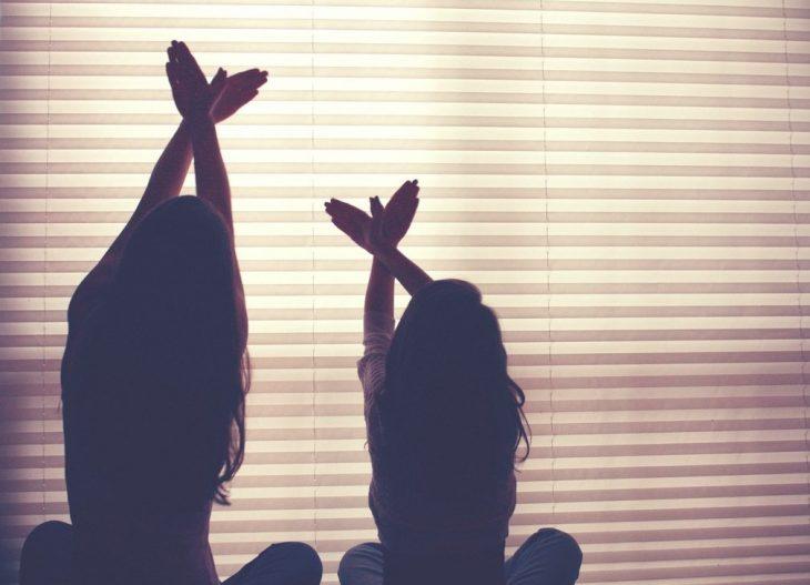 Hermanas haciendo poses en una ventana