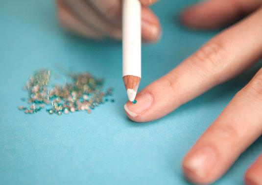 Colocando diamantes con delineador en las uñas