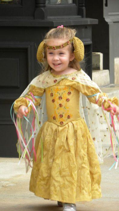 niña corriendo con un vestido amarillo y orejeras amarillas
