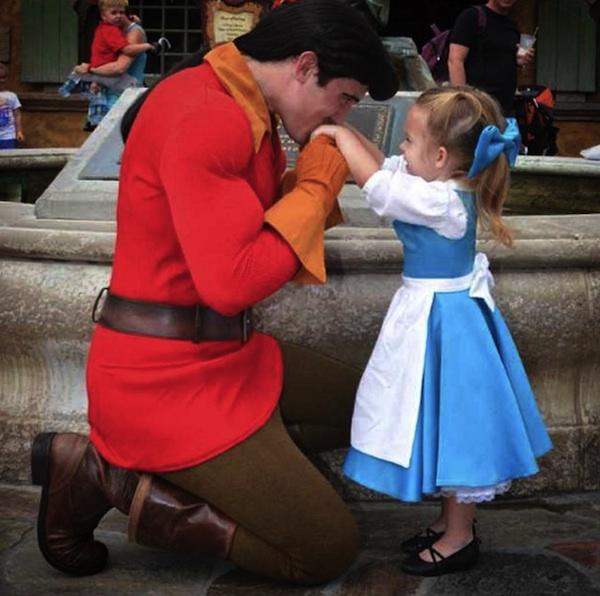 niña vestida de bella siendo besada en las manos por un príncipe de Disney