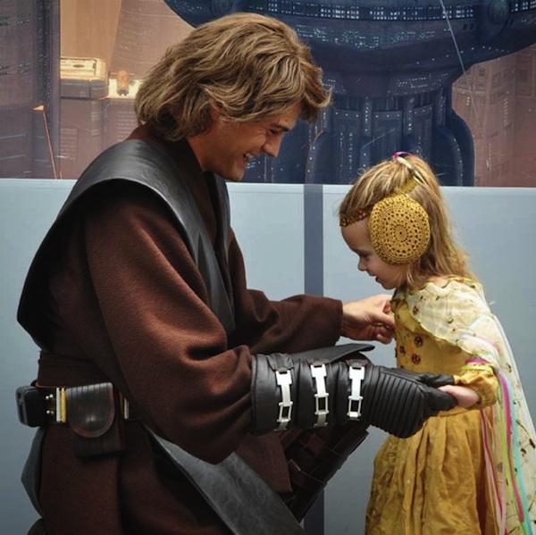 niña vestida de amarillo sostenida de las manos por un hombre disfrazado
