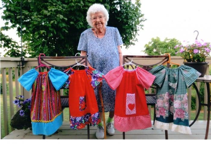 Una donna di 99 anni con alcuni degli abiti che produce ogni giorno