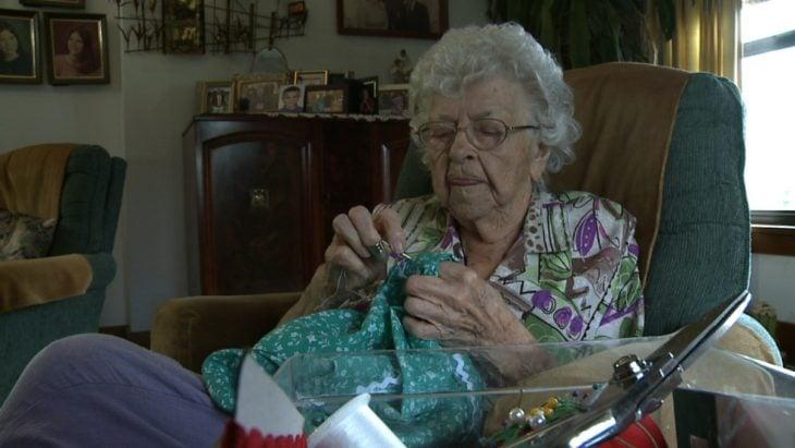 Mujer de 99 años sentada cosiendo un vestido