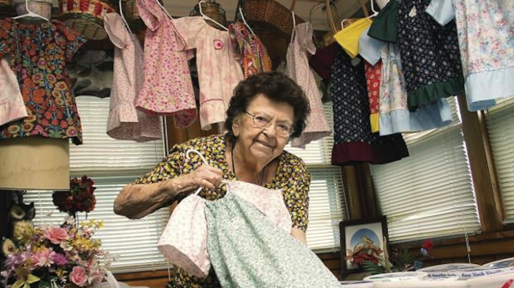 Lillian Weber circondata da alcuni abiti fatti da lei