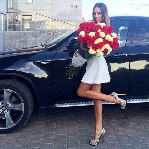 chica vestida de blanco sosteniendo un ramo de rosas frente a una camioneta negra