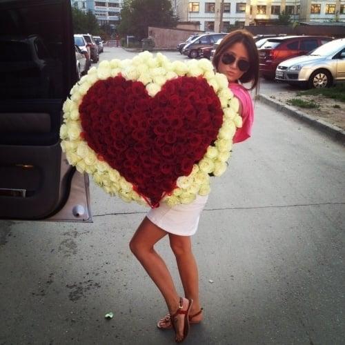 mujer sosteniendo un ramo de rosas en forma de corazón
