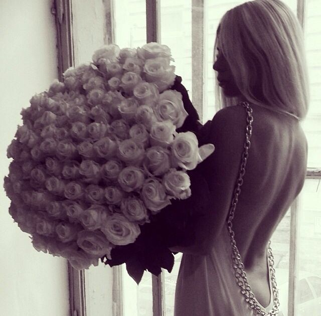 chica cargando ramo de rosas blancas con vestido color blanco con espalda descubierta