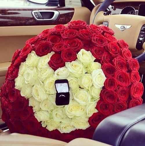 ramo de flores en forma de corazón rojas y blancas con un anillo dentro de ellas