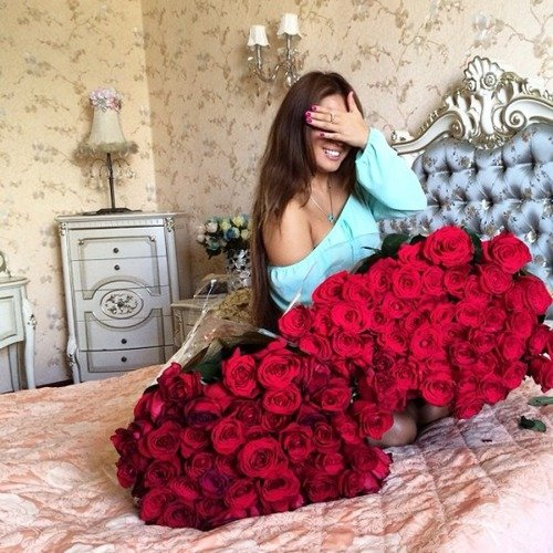 mujer sentada en medio de la cama cargando dos ramos de rosas rojas