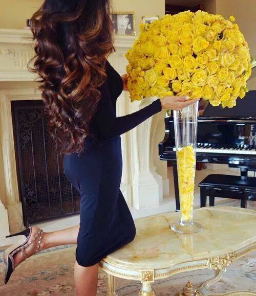 mujer de vestido azul y cabello suelto admirando unas rosas amarillas