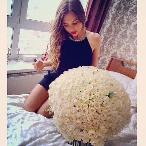 mujer hincada en medio de la cama observando un ramo de flores enorme