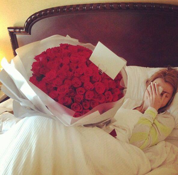 chica recostada en la cama mientras se sorprende al recibir rosas rojas con una tarjeta