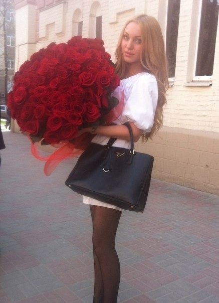 mujer en medio de la calle parada sosteniendo un gran ramo de rosas y su bolsa a un lado de ella