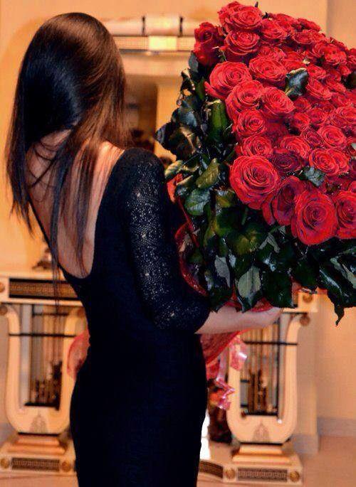 chica cargando un ramo de rosas vestida de negro
