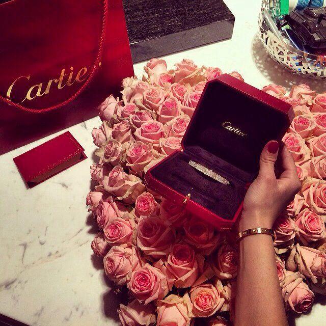 ramo de rosas con una joya de cartier frente a ellas