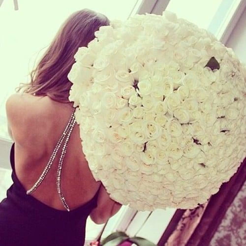 mujer de espaldas sosteniendo un ramo de rosas blancas