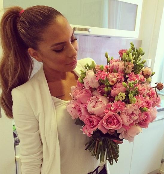 mujer vestida de blanco viendo un ramo de rosas rosas