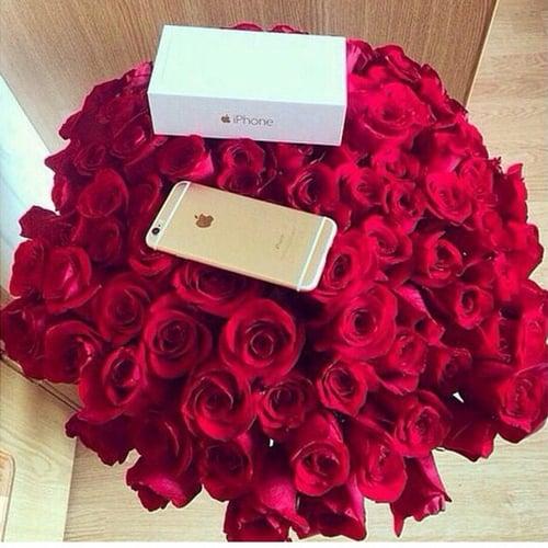 arreglo de flores con un iphone sobre ellas