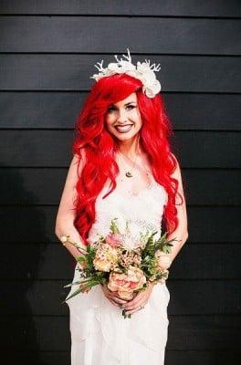 chica de cabello rojo vestida de novia sujetando un ramo de rosas