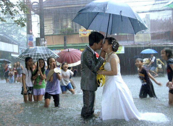 novios parados besandose en medio de una inundación con personas al rededor