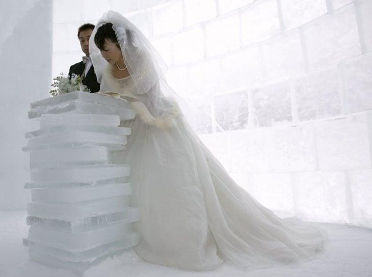 pareja de novios firmando una acta que esta sobre una pila de hielo mientras ellos están en un iglu
