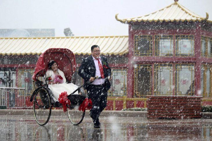hombre jalando un trineo con su esposa dentro de el mientras esta nevando