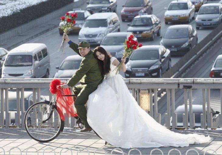 novios sobre una bicicleta parados en medio de un puente
