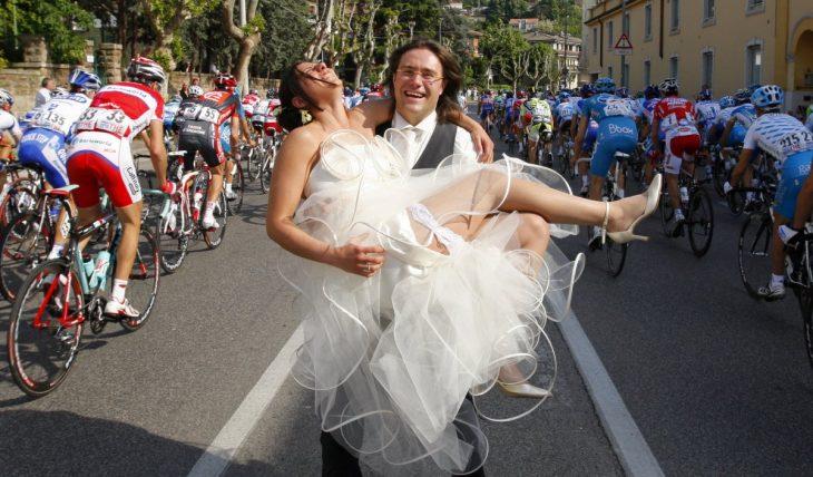 novio cargando a la novia en medio de un maratón de ciclismo