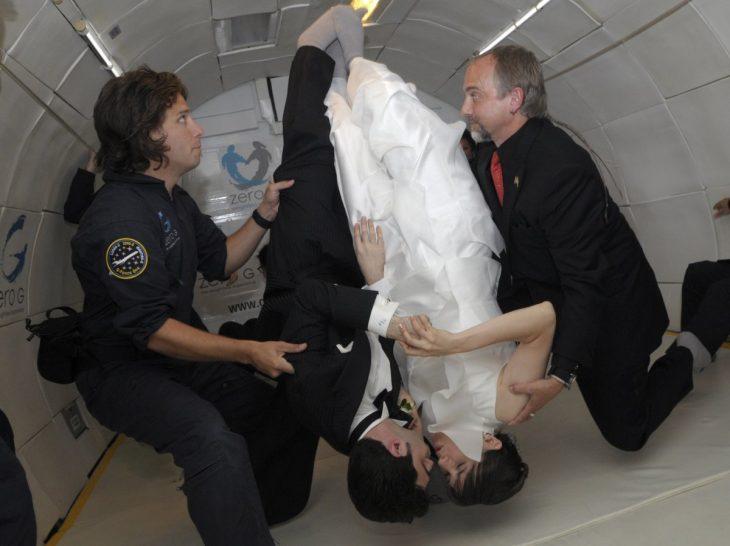 novios casándose en una nave espacial sostenidos por ayudantes del vuelo
