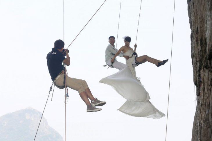 novios siendo fotografiados mientras cuelgan en un acantilado