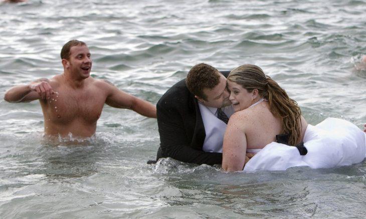 novios besandose en medio del mar