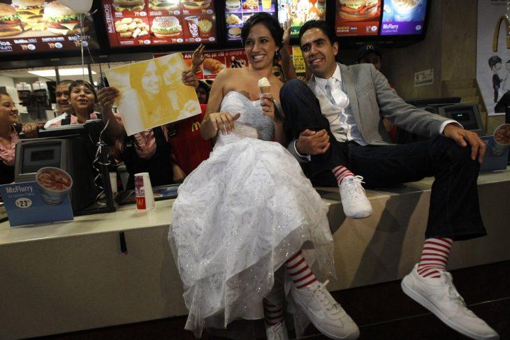 novios sentados en la barra de mcdonald's mientras comen un helado