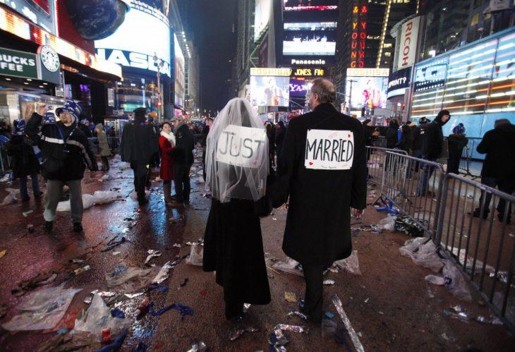 personas caminando por una calle de new york con un letrero en la espalda de recién casados