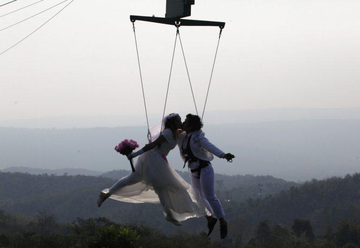 novios suspendidos en el aire sostenidos por cables mientras se besan