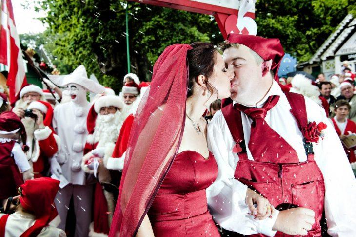 novios vestidos de rojo celebrando su boda junto a personas vestidas de santa claus