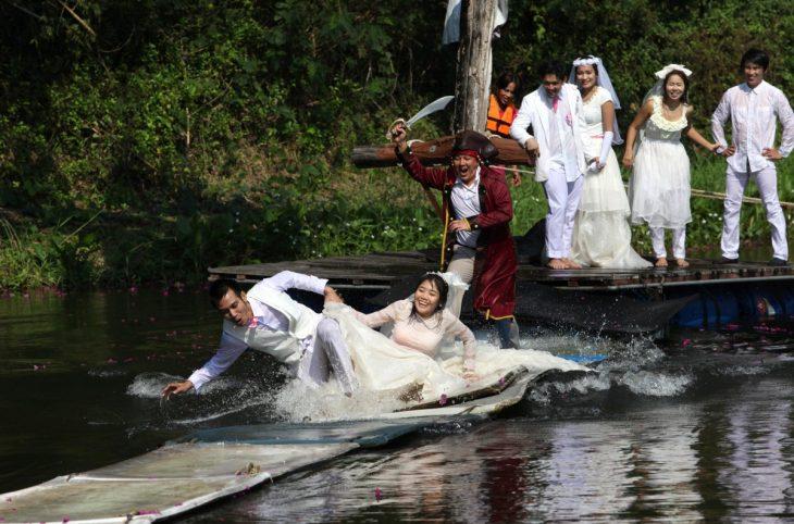 novios corriendo a través del agua siendo perseguidos por un señor vestido de pirata