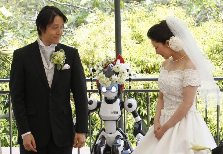 novios en una ceremonia de boda siendo casados por un robot