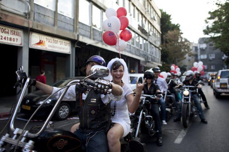 novia sentada en el asiento trasero de una motocicleta