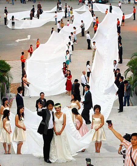 novios parados en la calle mostrando la cola del vestido de novia más largo