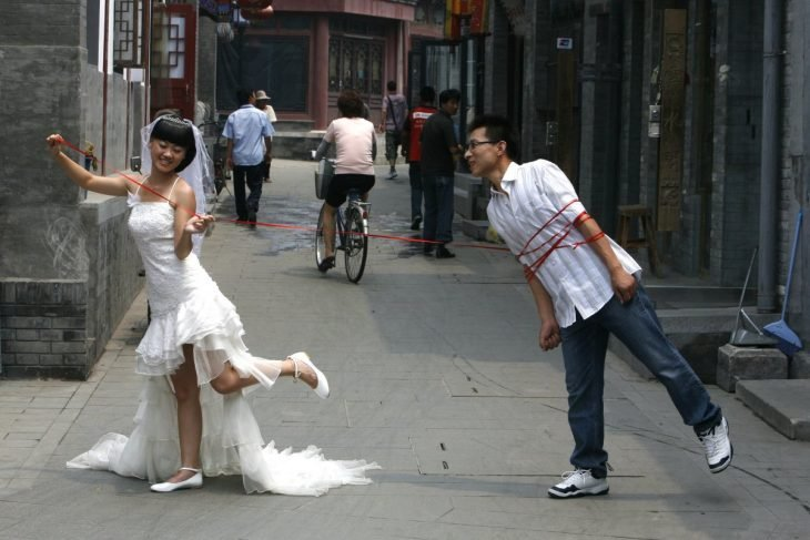 novia atando con un cordón a su novio en un callejón transitado