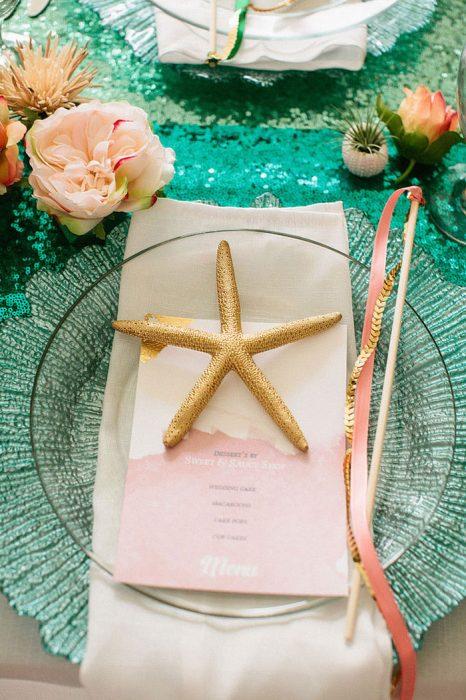 estrella de mar sobre un plato en una mesa con mantel de color verde y flores blancas