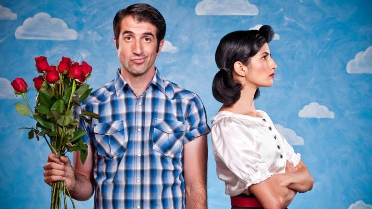 hombre sosteniendo ramo de rosas mientras  la mujer esta de espaldas