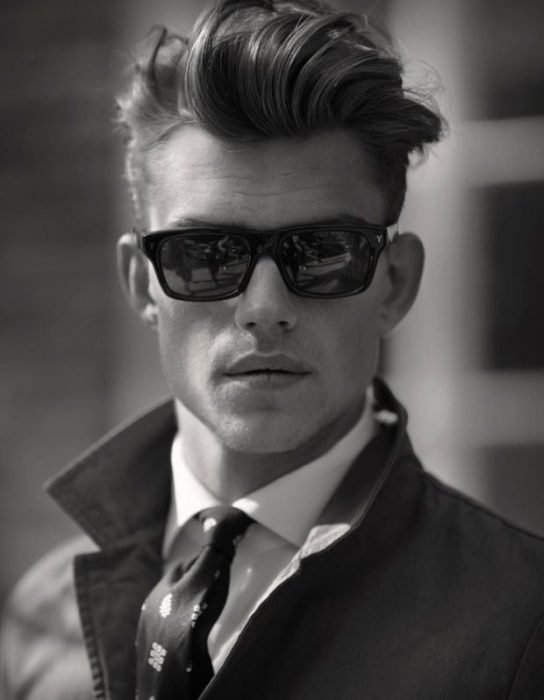 hombre vestido elegante con saco y corbata y usando lentes de sol