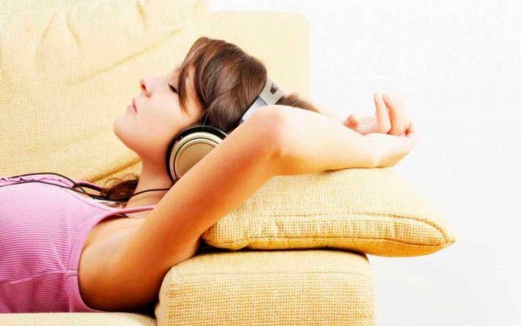 mujer acostada en un sillon con audífonos escuchando música