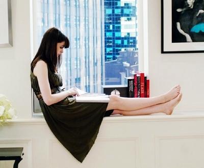 chica sentada cerca de la ventana leyendo un libro mientras tiene los pies estirados