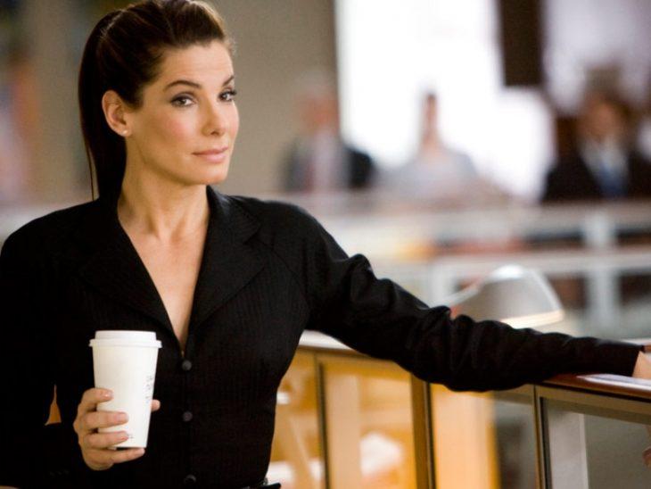 mujer vestida con traje color negro sosteniendo un café en su mano mientras esta en la oficina
