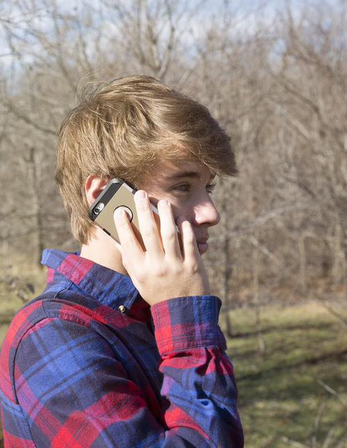chico rubio hablando por teléfono en medio de un gran campo
