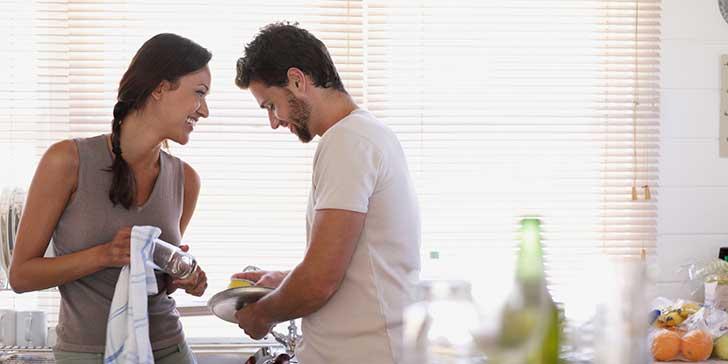 pareja de novios lavando los platos y conversando